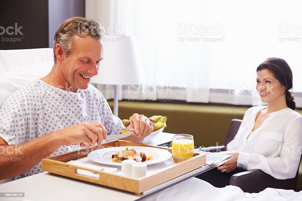 Male Patient In Hospital Bed Eating Meal From Tray stock photo
