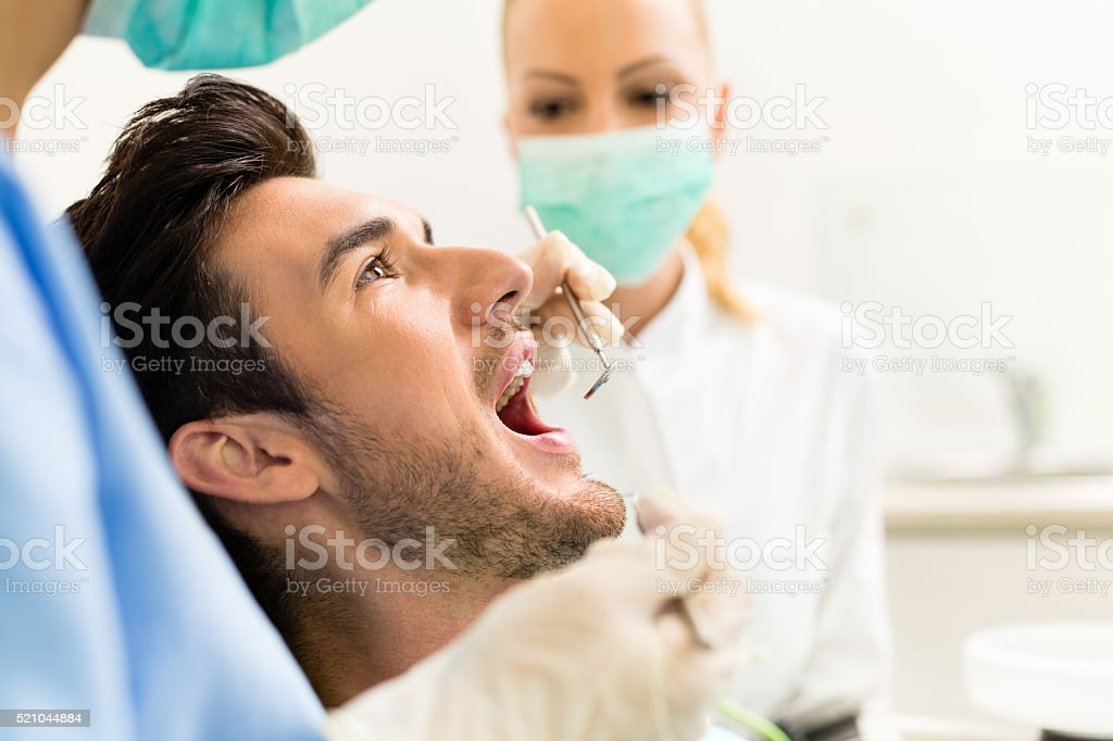 Male patient opening mouth before oral inspection at dentist's office stock photo