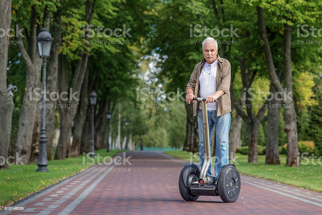 Male pensioner riding modem vehicle stock photo