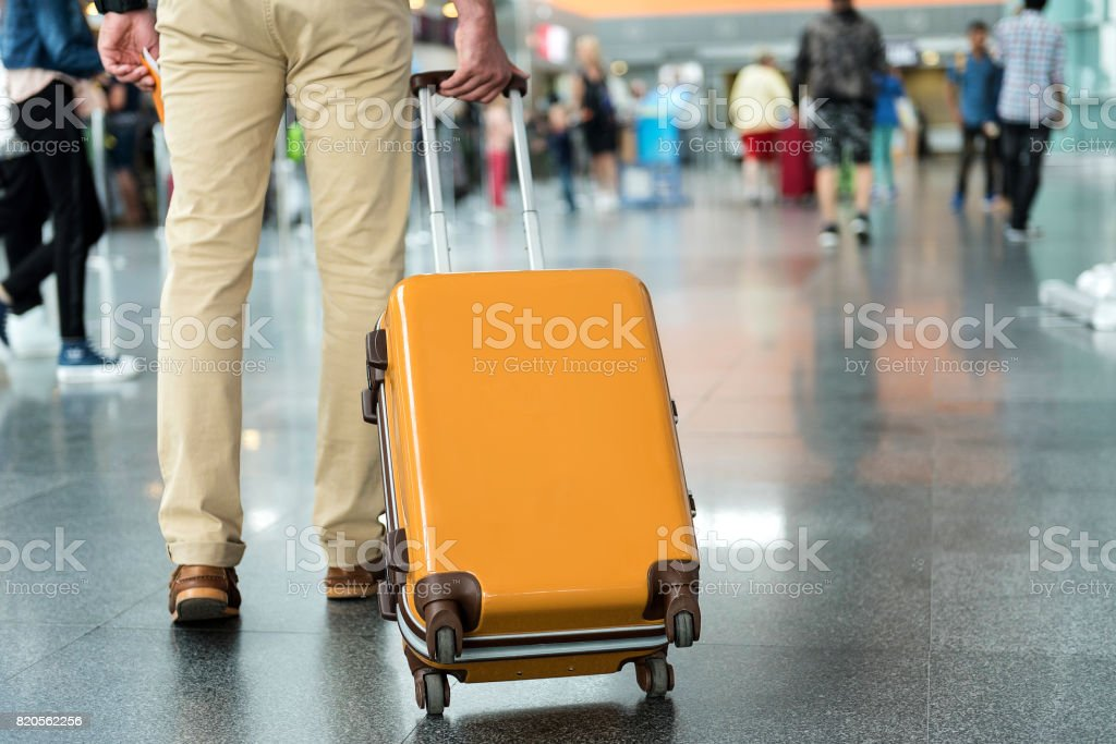 Male person holding handle of baggage stock photo