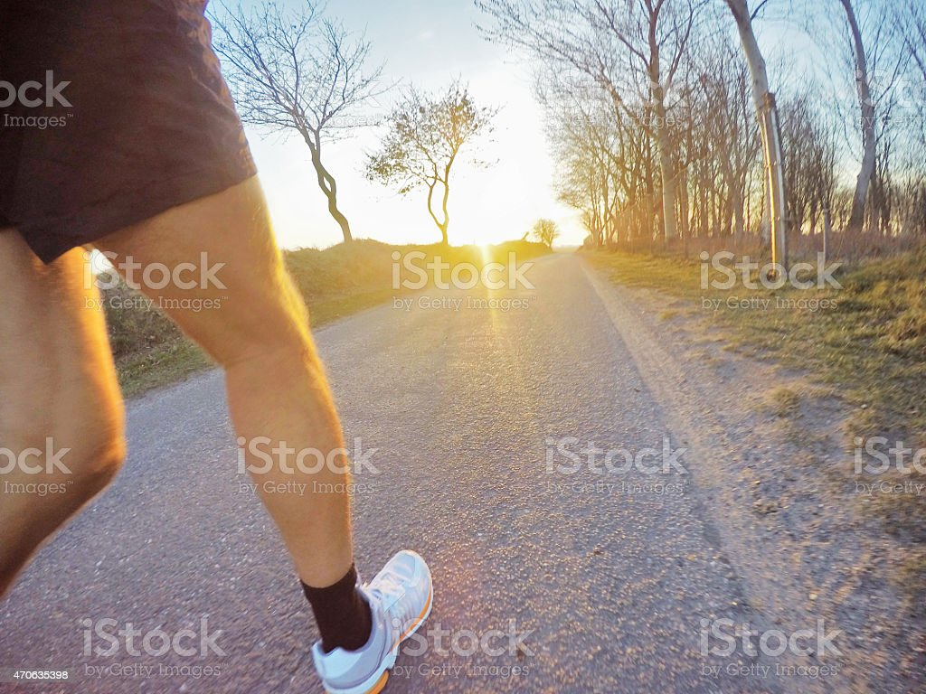 Male person jogging at sunset on tarr road, GoPro image stock photo