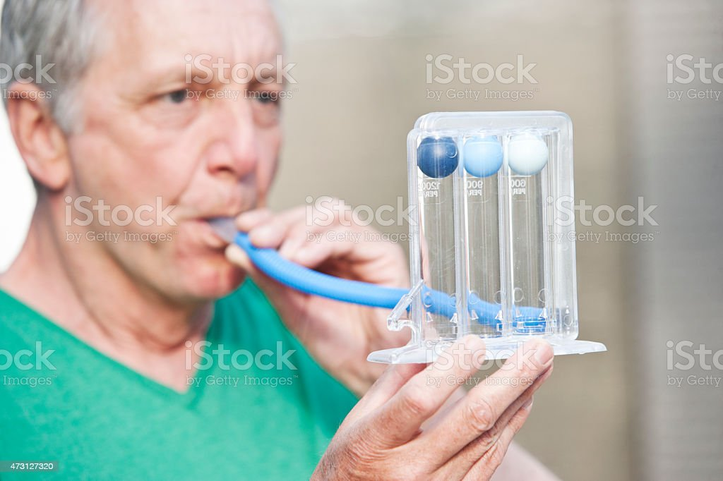 Male person performing lung function test by using a triflow stock photo