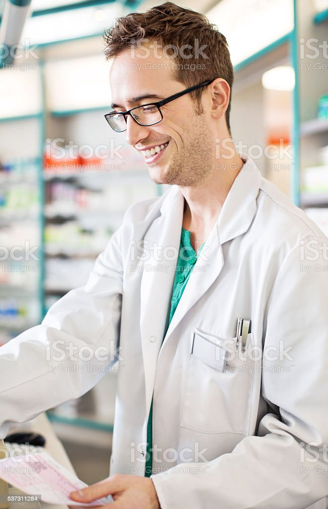 Male pharmacist with prescription at pharmacy counter stock photo