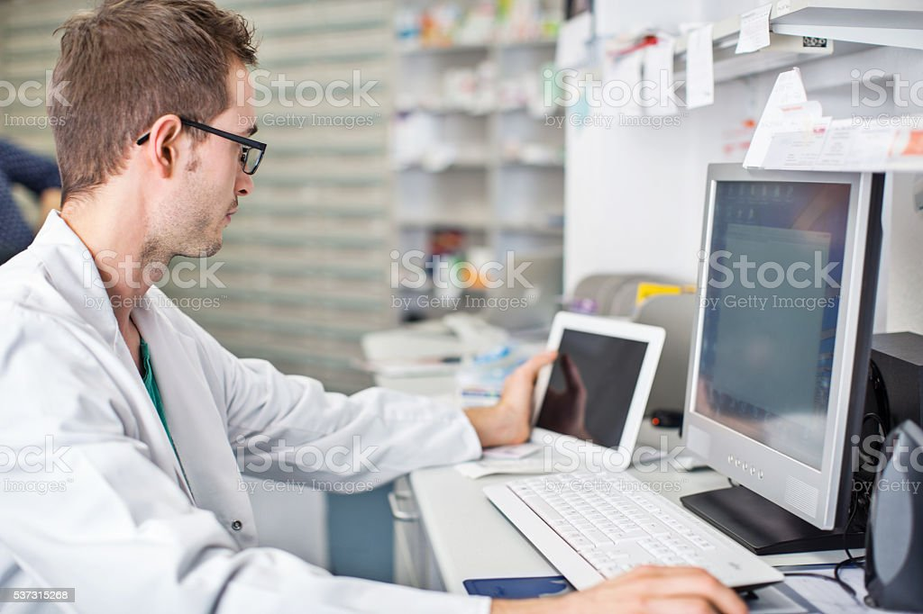 Male pharmacist working at his desk stock photo