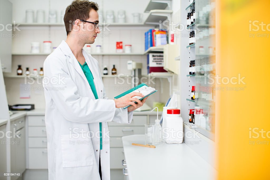 Male pharmacist working at the chemist store stock photo