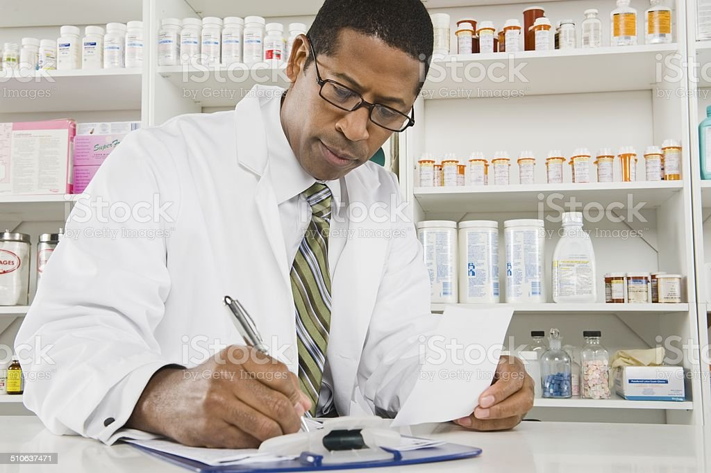Male pharmactist working in pharmacy stock photo