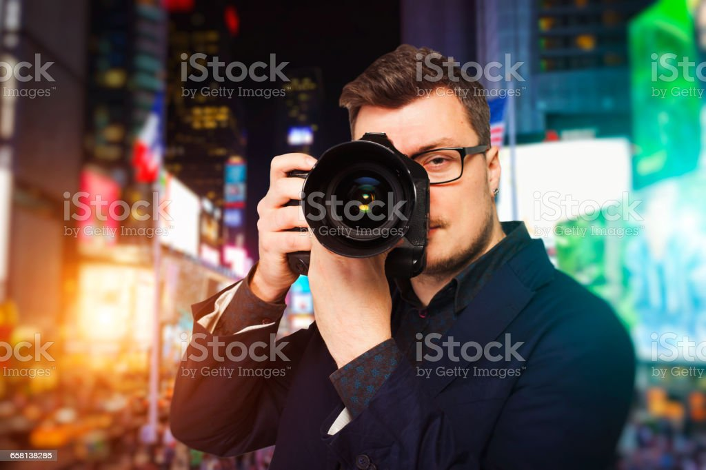 Male photographer in glasses with digital camera stock photo