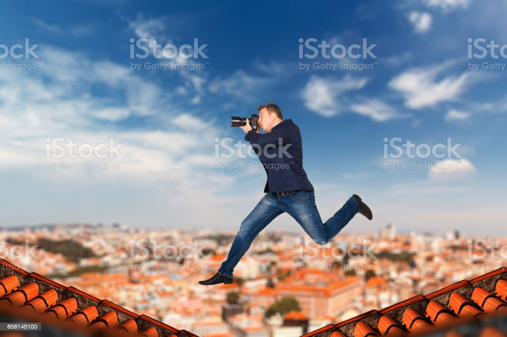 Male photographer jumping on the roofs of houses stock photo