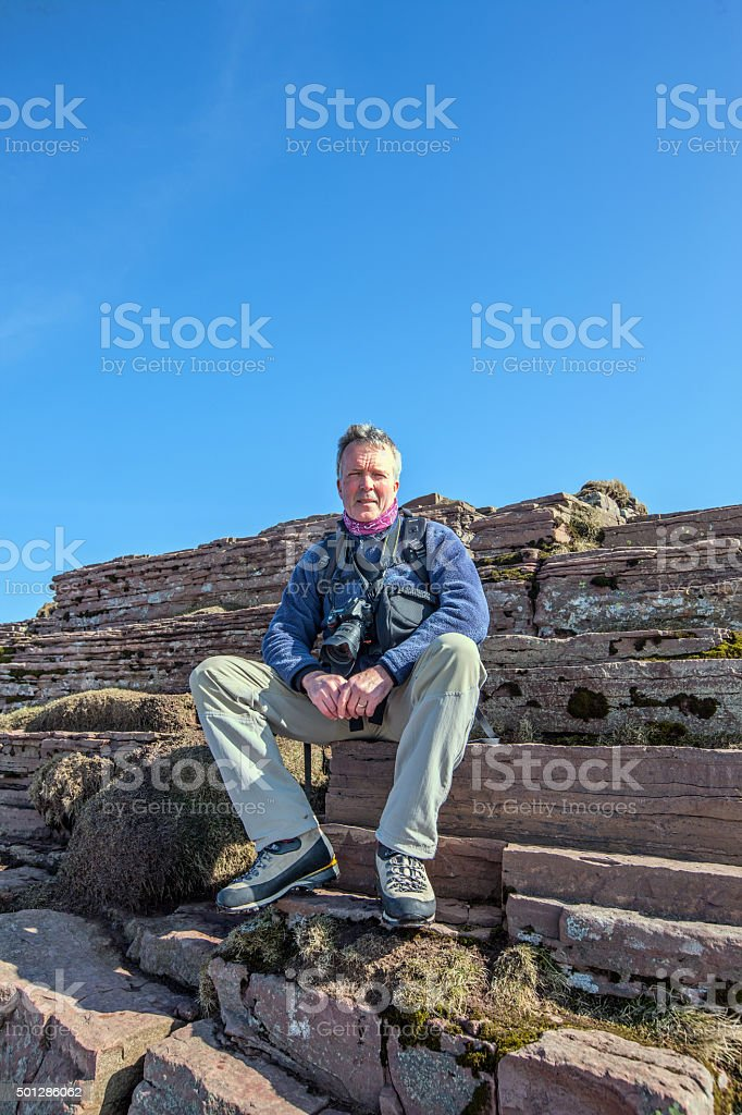 Male photographer on ledge of snow covered mountain stock photo