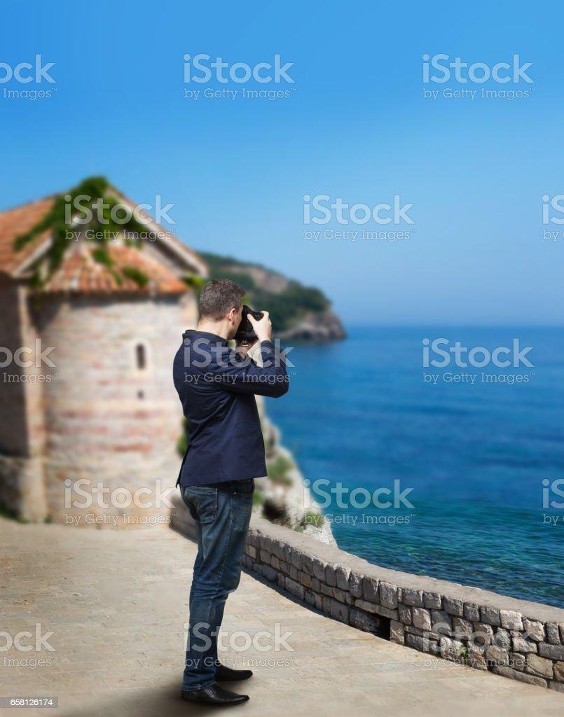 Male photographer taking picture of sea coast stock photo