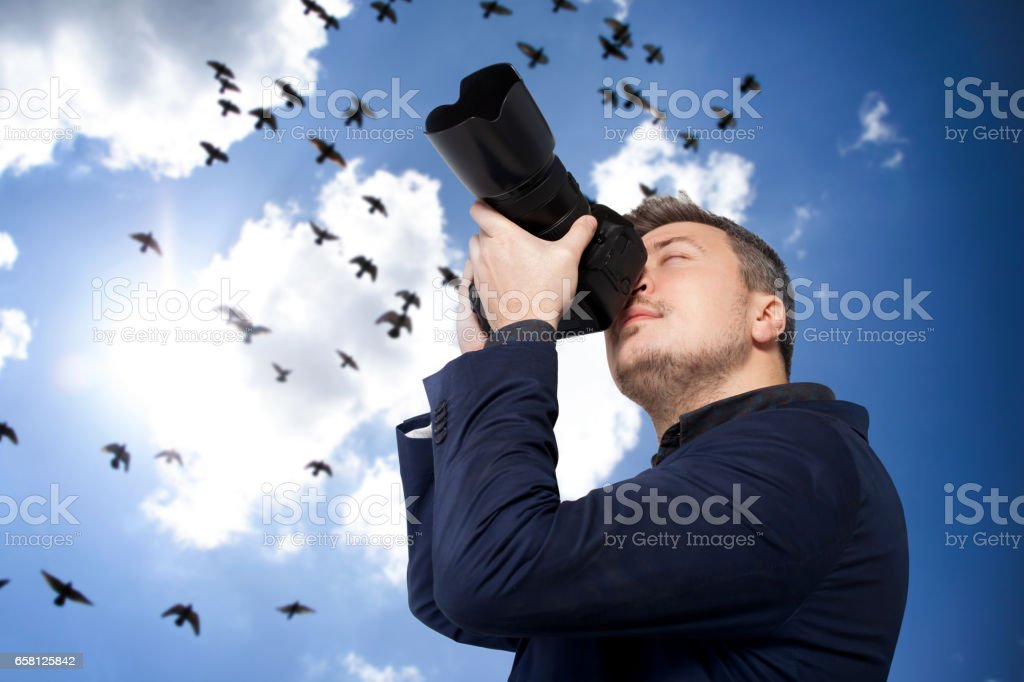 Male photographer with camera, birds on background stock photo