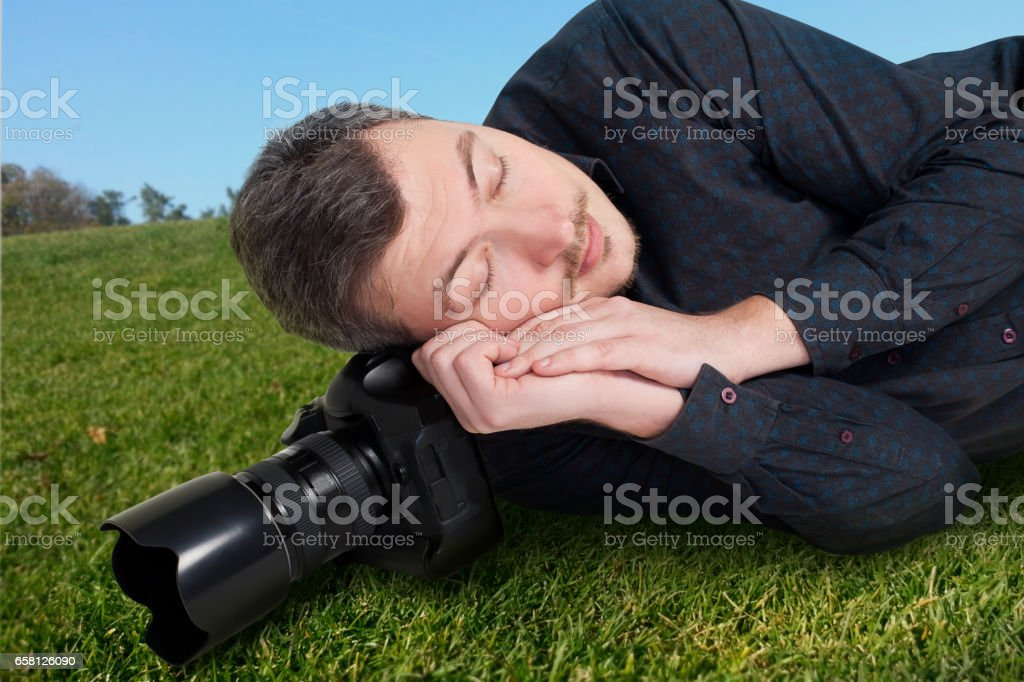 Male photographer with camera sleeping on meadow stock photo