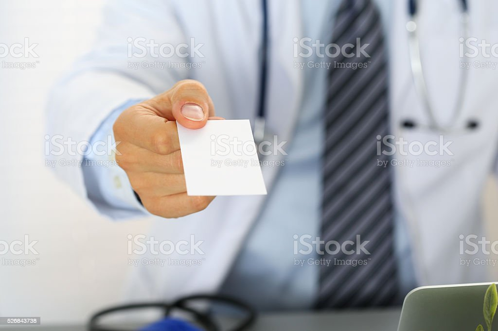 Male physician hand holding and giving white blank calling card stock photo