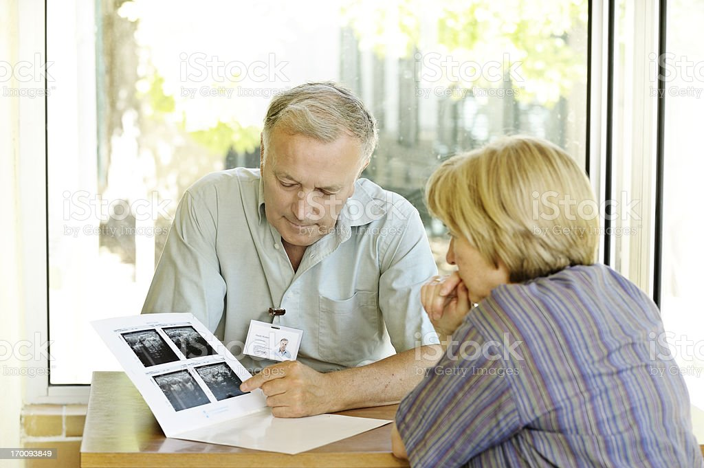 Male physician specialist explaining scans to female patient stock photo