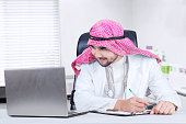 Male physician works with laptop in clinic