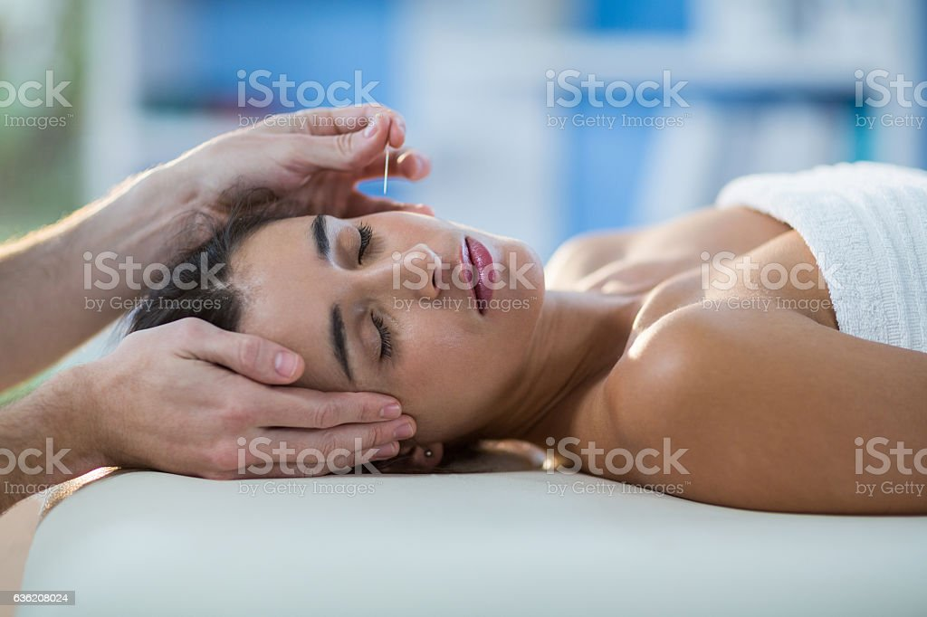 Male physiotherapist giving head massage to female patient stock photo