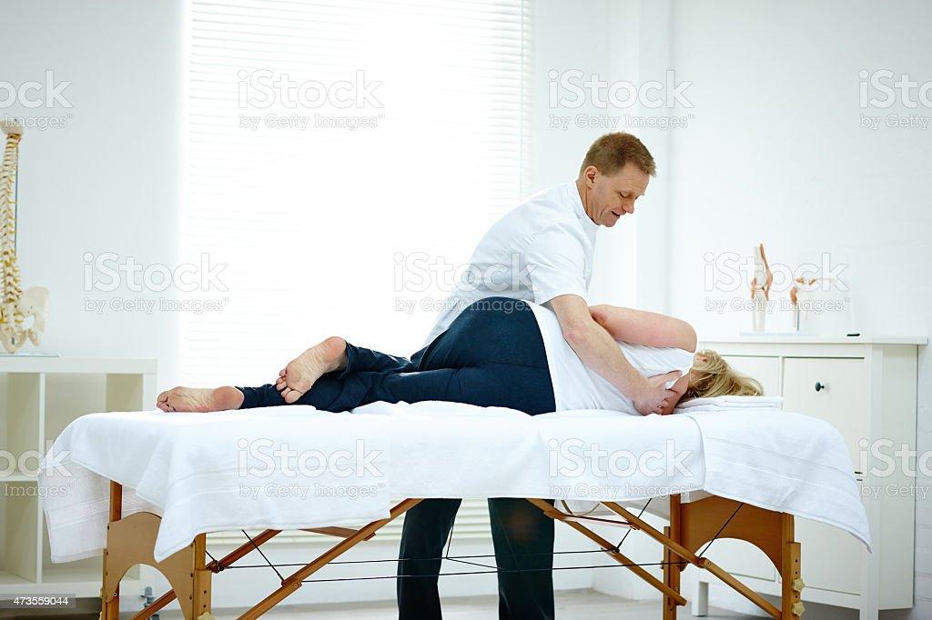 Male physiotherapist massaging a senior woman's back stock photo