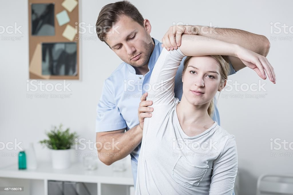 Male physiotherapist training with patient stock photo