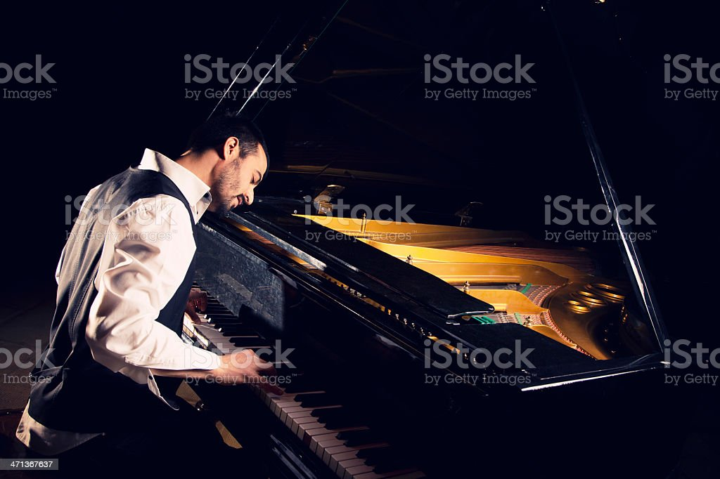 A male pianist playing a grand piano stock photo