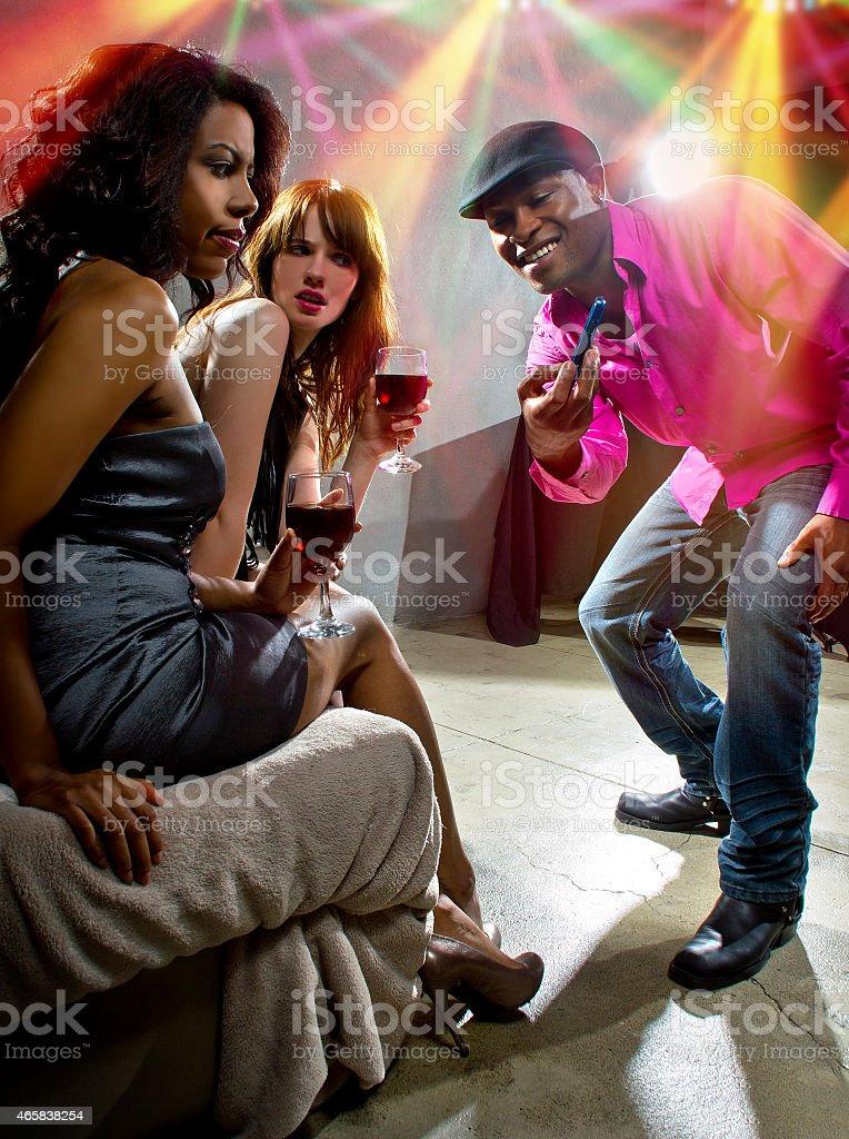 Male Pickup Artist Harassing Women at a Nightclub stock photo