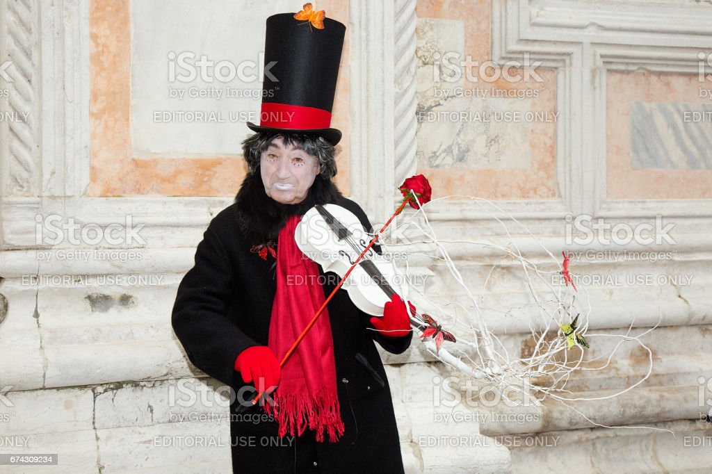 Male Pierrot playing violin with red rose on San Zaccaria Square - Venice Carnival stock photo