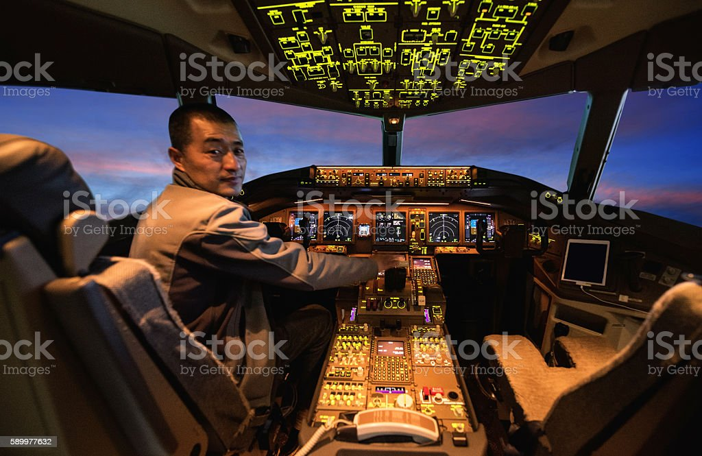 Male Pilot in Airplane Cockpit stock photo