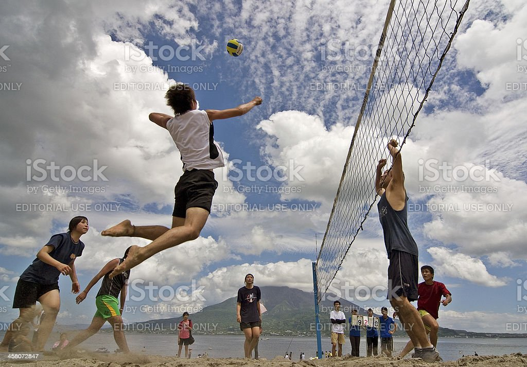 Male  player jumps to spike at  a beach volleyball competition royalty-free stock photo