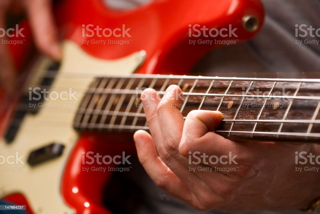 A male playing a red and white bass stock photo