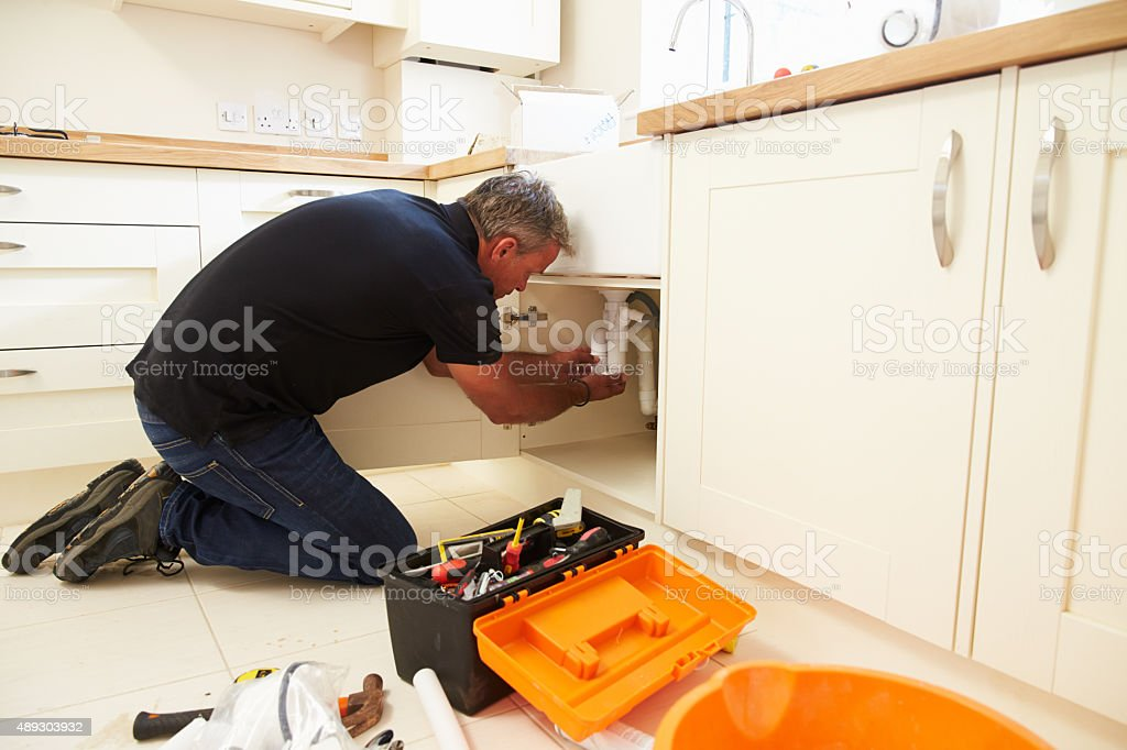 Male plumber fixing a kitchen sink stock photo