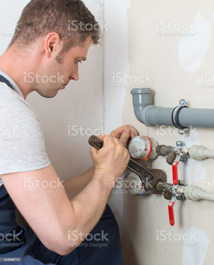 Male plumber fixing water meter with adjustable wrench. stock photo