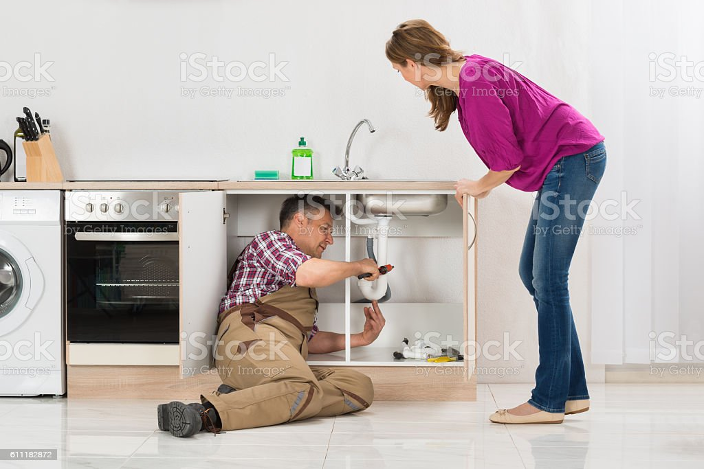 Male Plumber Repairing Pipe Under Sink In Kitchen stock photo