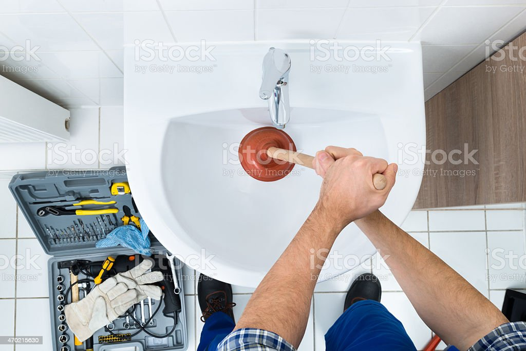 Male Plumber Using Plunger In Bathroom Sink stock photo