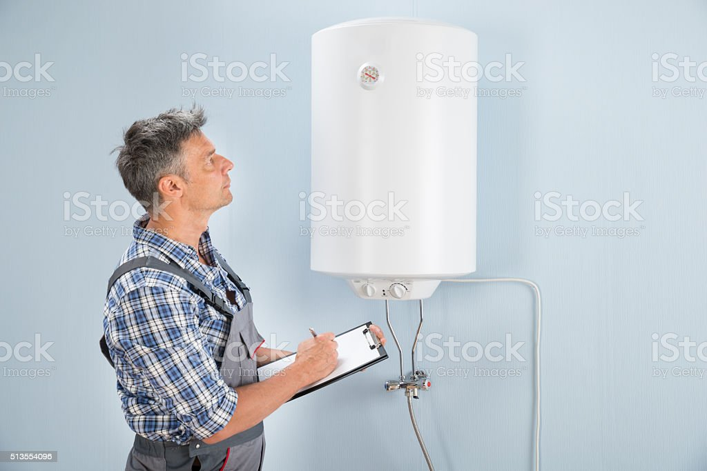 Male Plumber With Clipboard Looking At Electric Boiler stock photo