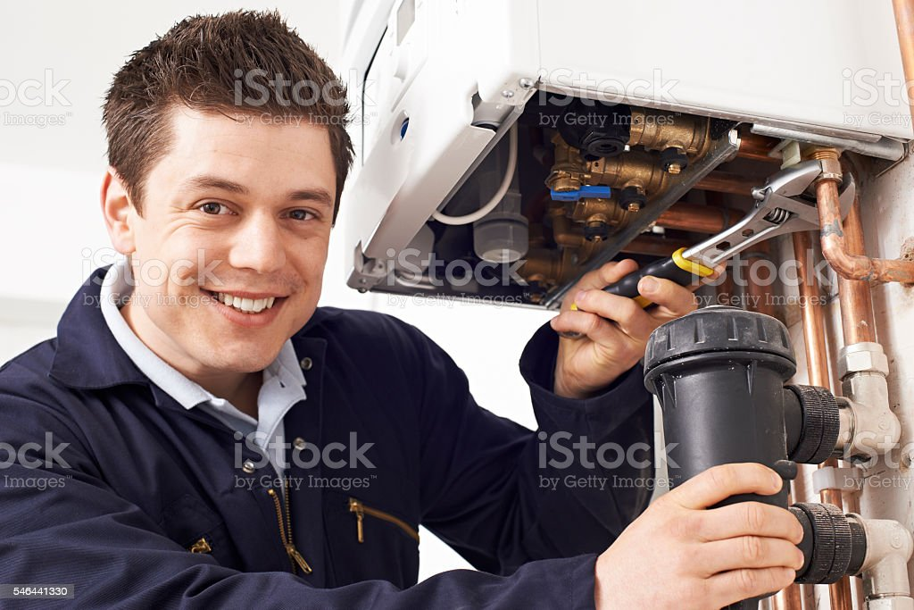 Male Plumber Working On Central Heating Boiler stock photo