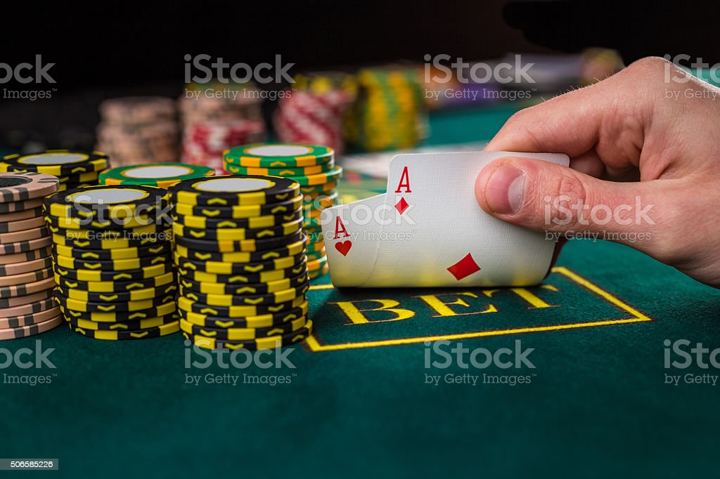 Male poker player lifting the corners of two cards aces stock photo