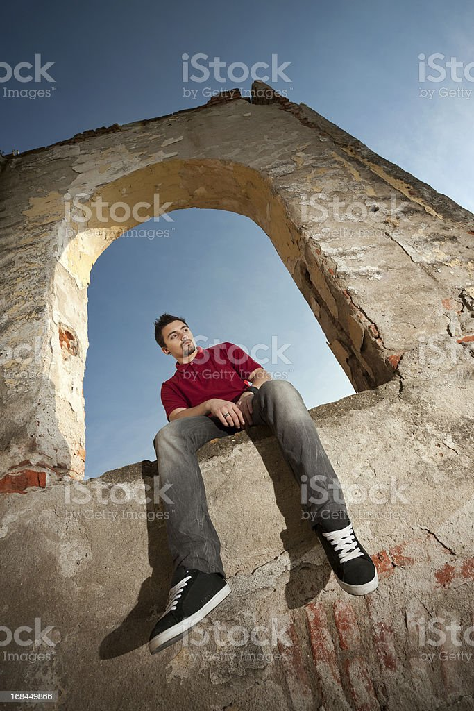 Male posing in an arch of abandoned building royalty-free stock photo