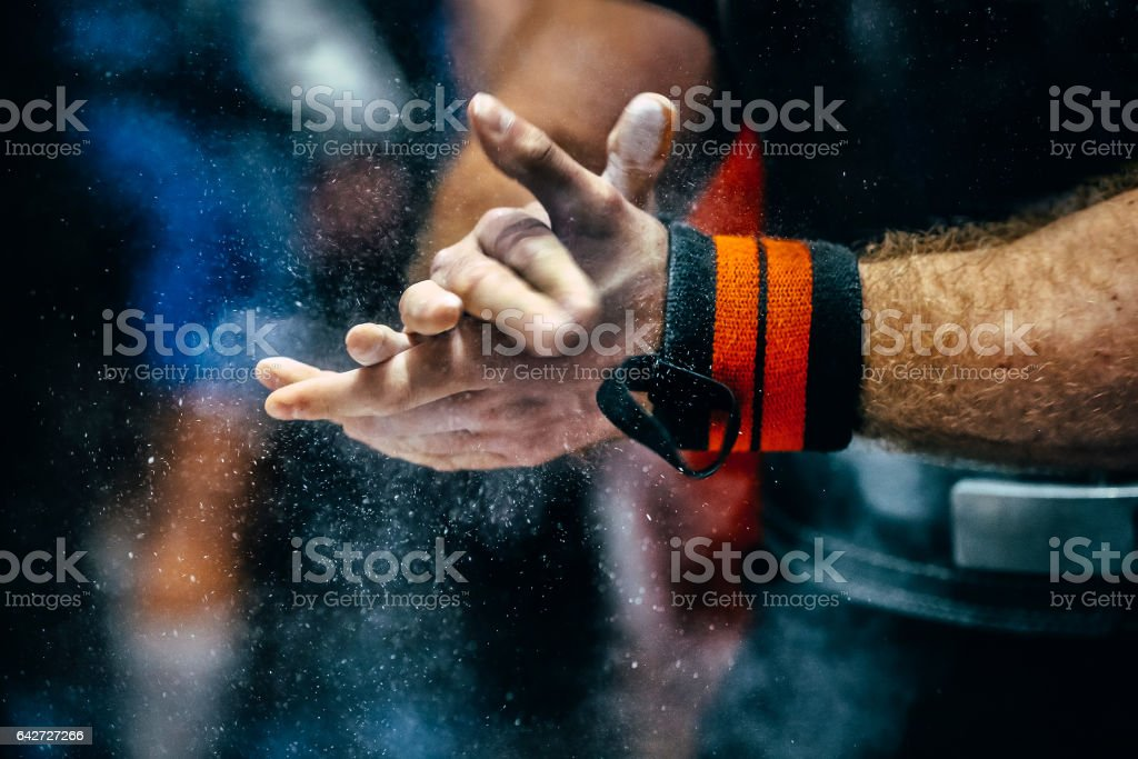 male powerlifter hand in talc and sports wristbands preparing to bench press stock photo