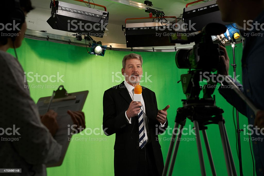 Male Presenter In Television Stdio With Crew In Foreground stock photo