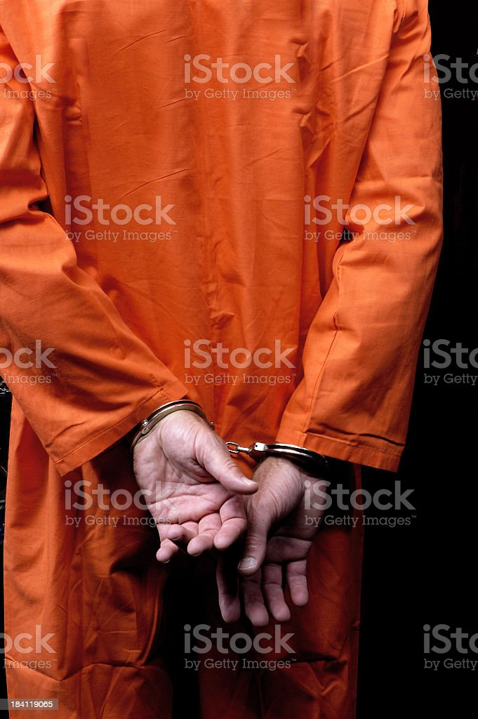Male prisoner in orange suit his arms handcuffed behind back stock photo