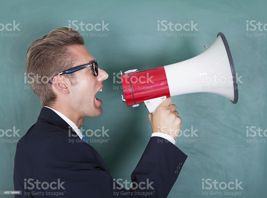 Male Professor Shouting Though Megaphone stock photo