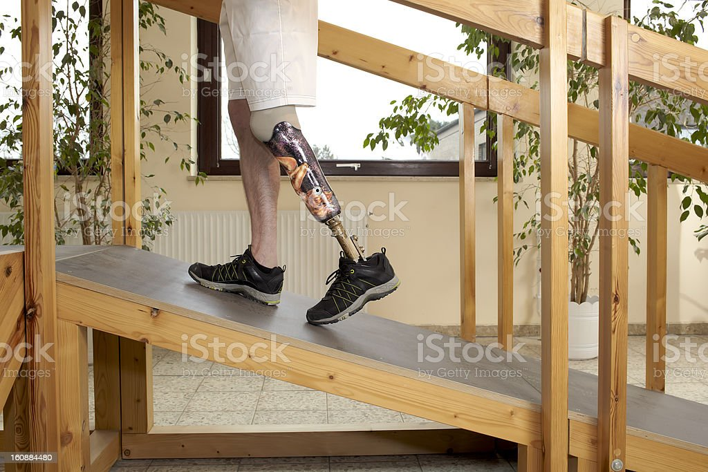 Male prosthesis wearer training to climb a slope stock photo