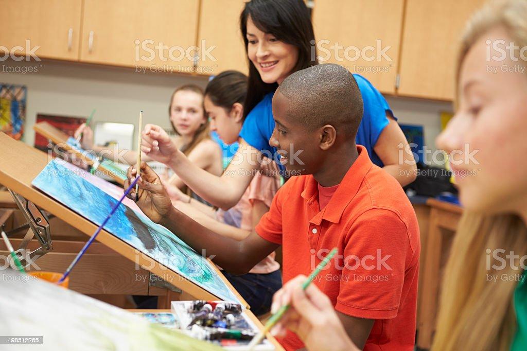 Male Pupil In High School Art Class With Teacher stock photo