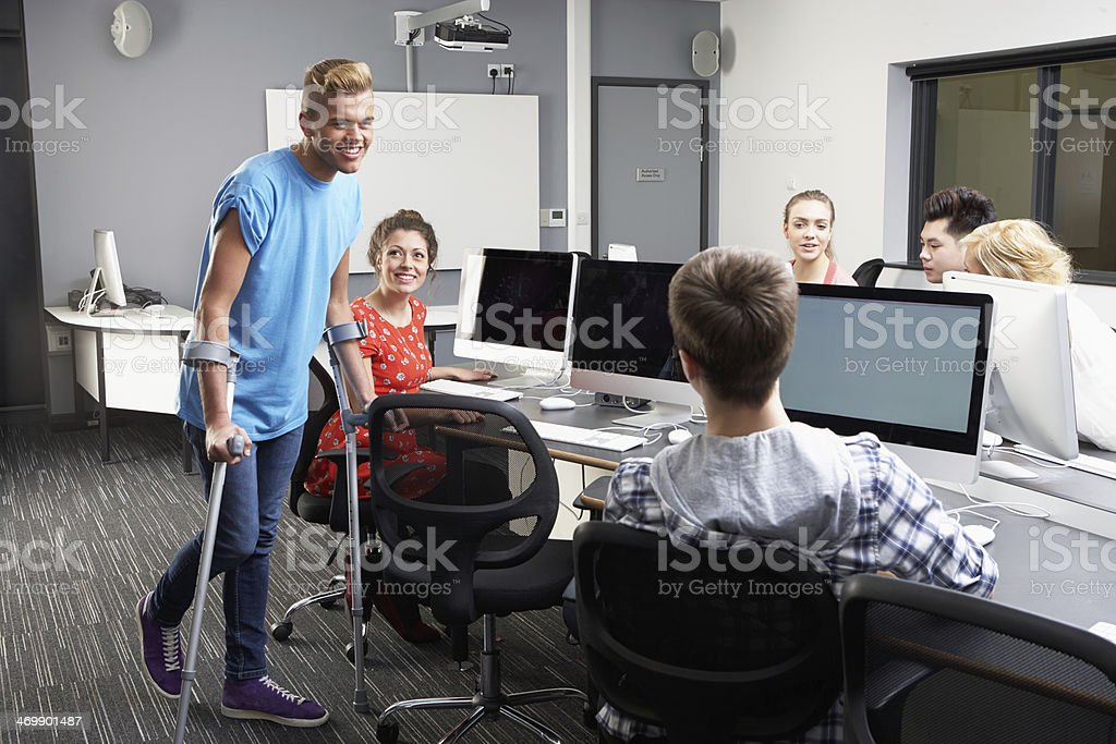 Male Pupil Walking On Crutches In Computer Class stock photo