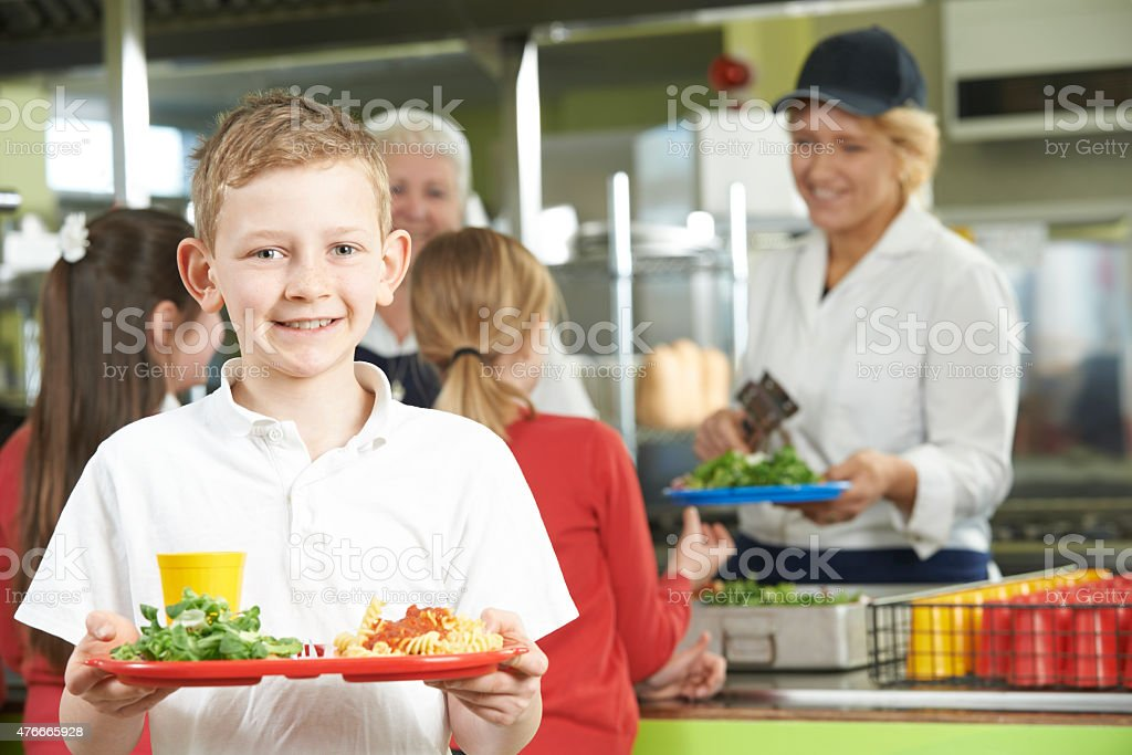 Male Pupil With Healthy Lunch In School Cafeteria stock photo