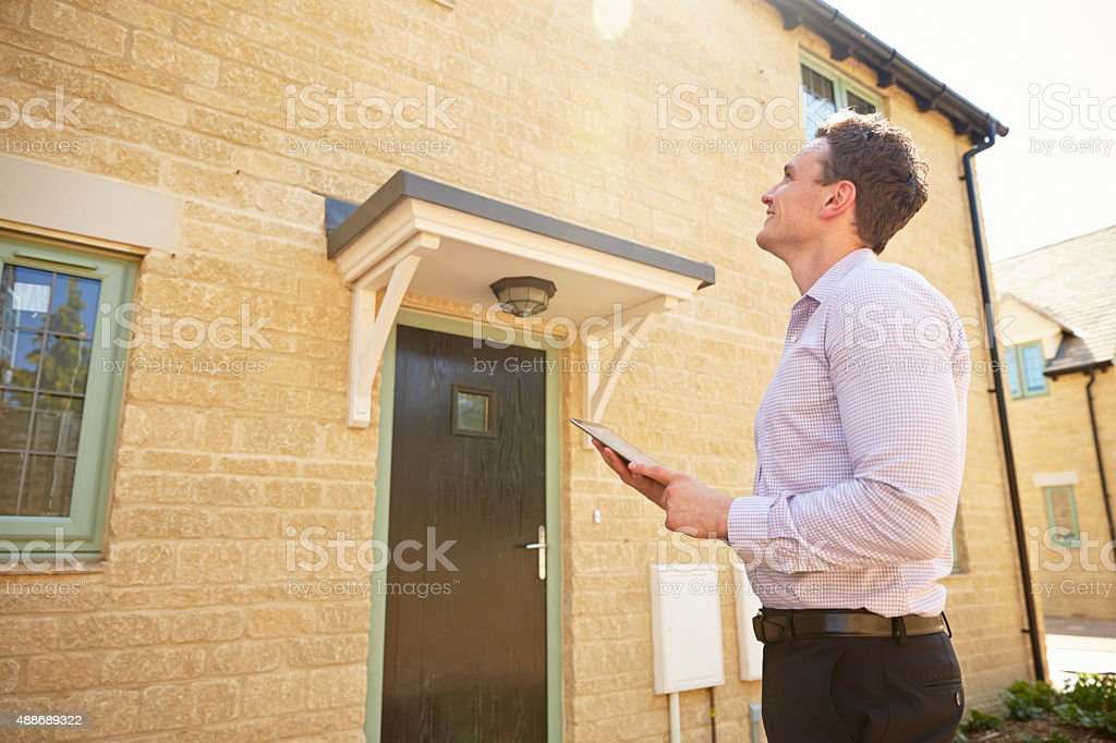 Male real estate agent looking up at a house exterior stock photo