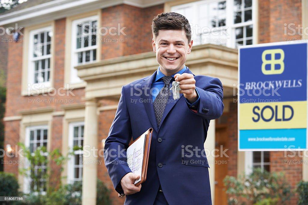Male Realtor Standing Outside Residential Property Holding Keys stock photo