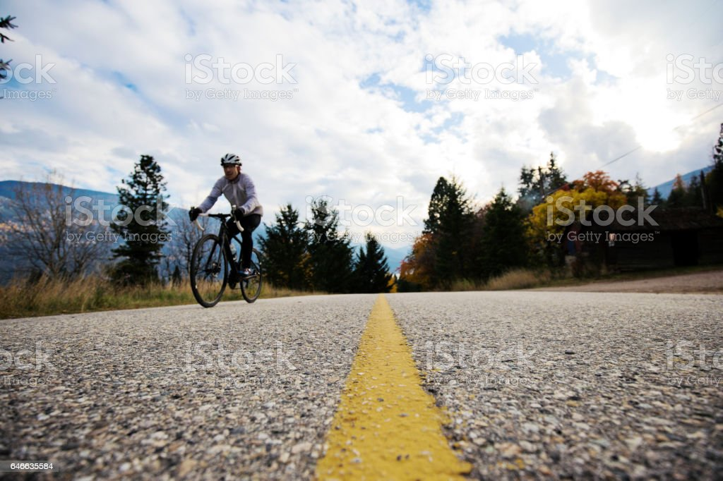 A male road cyclist rides along a country road in British Columbia, Canada in the fall. stock photo