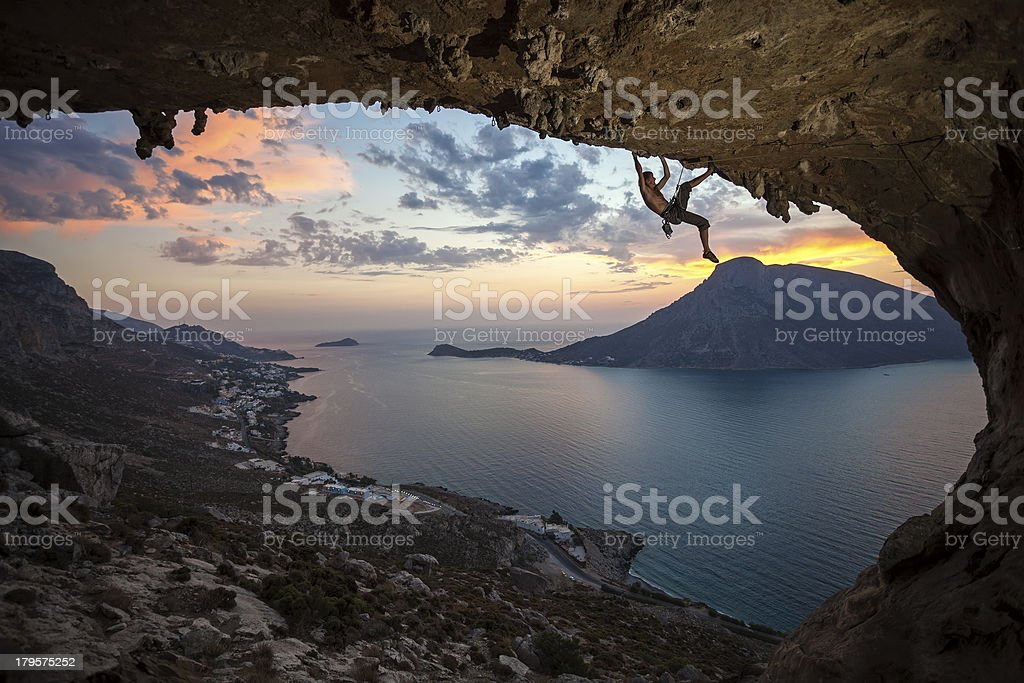 Male rock climber against picturesque view at sunset stock photo