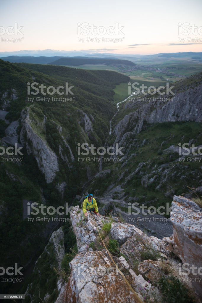 Male rock climber ascending on steep mountain during sunset stock photo