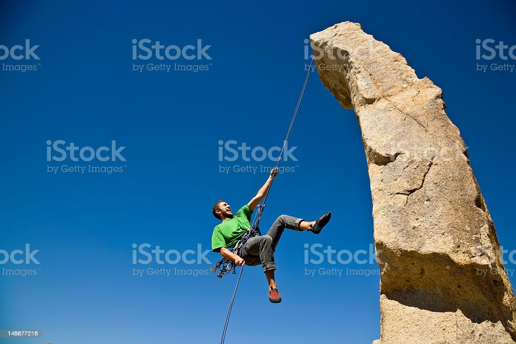 A male rock climber rappelling stock photo